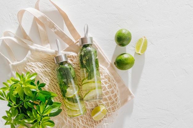 Acqua fresca infusa di lime e menta, cocktail, bevanda detox, limonata in bottiglie riutilizzabili con sacchetti ecologici. ecologico. stile di vita sostenibile.