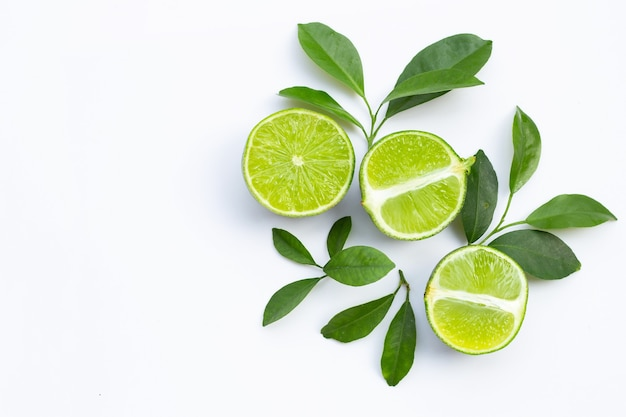 Limette fresche con foglie verdi su sfondo bianco. vista dall'alto