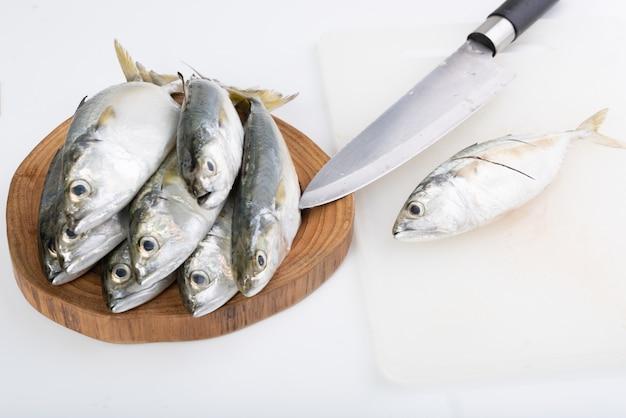 Pesce e coltello freschi dello sgombro sul tagliere di legno su bianco
