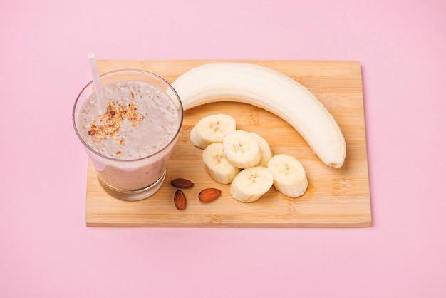 Frullato di banana fresco in un bicchiere su sfondo rosa