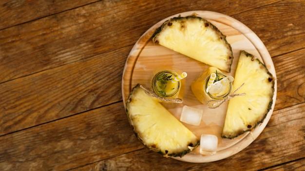Succo di ananas fatto fresco con ghiaccio in una piccola bottiglia di vetro su fondo di legno. bevanda fatta in casa. vista dall'alto