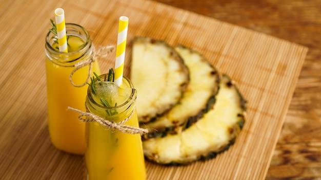 Succo di ananas fatto fresco con ghiaccio in una piccola bottiglia di vetro su fondo di legno. bevanda fatta in casa.
