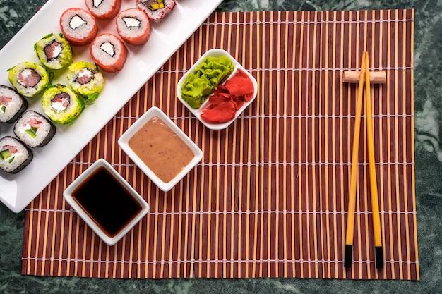 Set sushi roll preparato fresco con salsa di soia, salsa di sesamo, wasabi e zenzero sottaceto. cucina tradizionale giapponese.