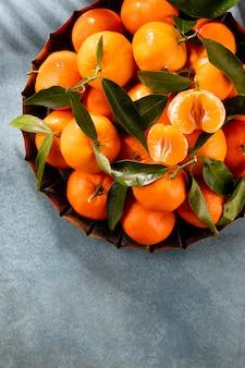 Mandarini freschi frutta o mandarini con foglie in una scatola di legno, vista dall'alto