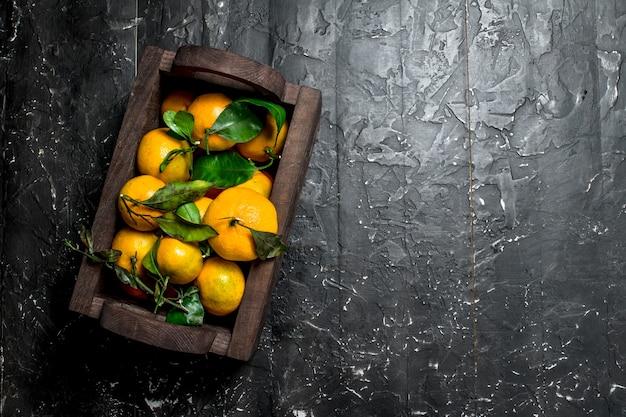 Mandarini freschi nella confezione. su sfondo nero rustico
