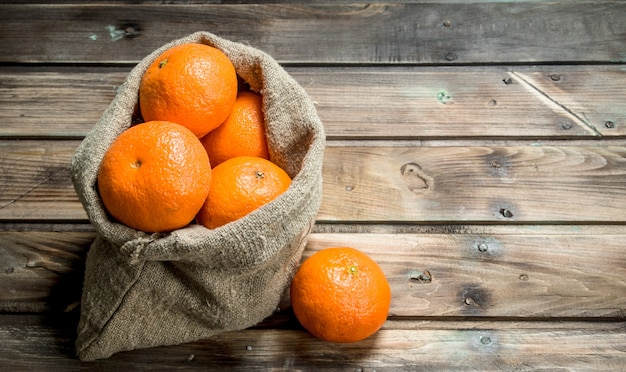 Mandarini freschi nel sacco. su legno