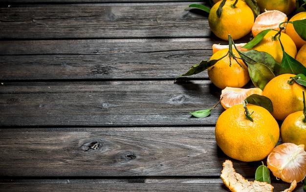 Mandarini freschi con foglie. su legno nero