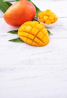 Mango fresco, bella frutta tritata con foglie verdi sul tavolo in legno luminoso