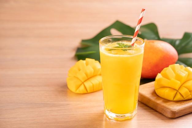 Succo di mango fresco con una bella polpa di polpa tritata su uno sfondo di tavolo in legno brillante