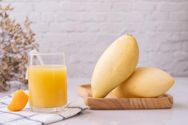 Succo di mango fresco con manghi maturi sul tavolo.