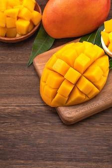 Mango fresco - succosi cubetti di mango tritati su tagliere di legno e fondo rustico in legno