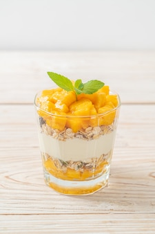 Yogurt fresco al mango con muesli in vetro - stile di cibo sano