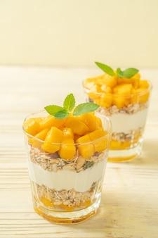Yogurt al mango fresco con muesli in vetro - stile di cibo sano