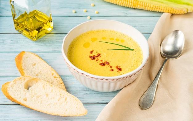 Zuppa di purea di mais latte fresco in un piatto bianco su sfondo blu decorato con una parrucca e giovani cipolle verdi. orientamento orizzontale. foto di alta qualità