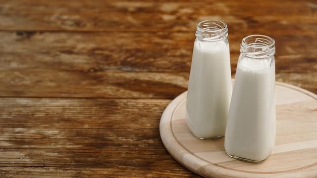 Latte fresco in due bottiglie di vetro. superficie rustica in legno. mangiare sano