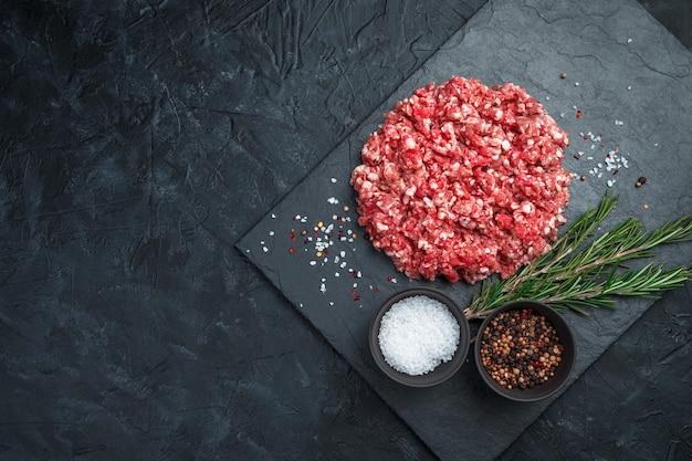 Carne fresca macinata con rosmarino e spezie su uno sfondo nero.
