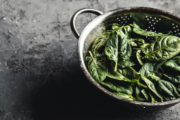 Mini spinaci freschi in uno scolapasta sul vecchio tavolo di cemento. cibo sano, prodotto ecologico. vegano