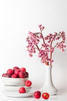 Natura morta minimal fresca con prugna ciliegia e fiori viola rosa sul tavolo nei toni della luce bianca