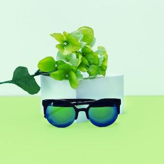 Misto fresco. occhiali da sole e fiori alla moda. accento verde.