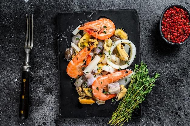 Fresco mix di frutti di mare cocktail con gamberi, gamberi, cozze, calamari e polpi. sfondo nero. vista dall'alto.