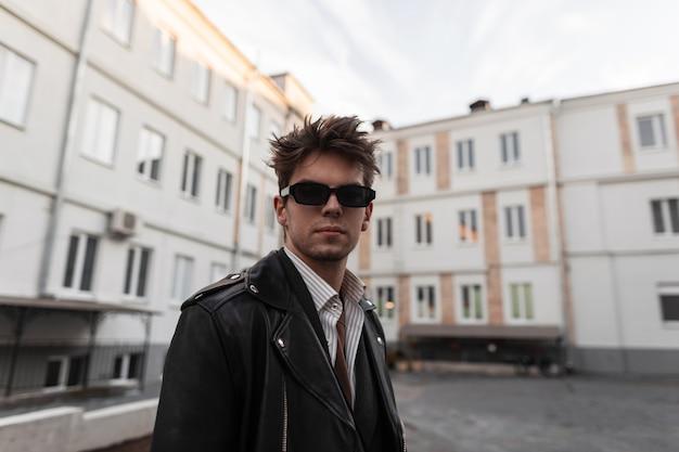 Fresco e moderno ritratto di un giovane hipster in eleganti occhiali da sole con acconciatura in giacca di pelle nera alla moda in strada. modello americano bel ragazzo in posa all'aperto. abbigliamento da uomo alla moda.