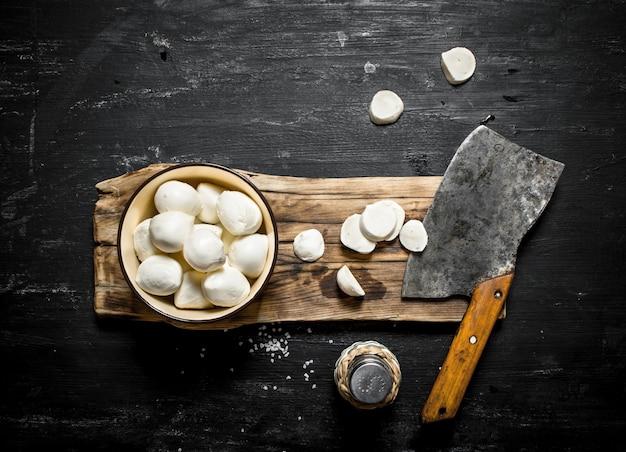 Mozzarella fresca con un'accetta per il taglio su un fondo di legno nero