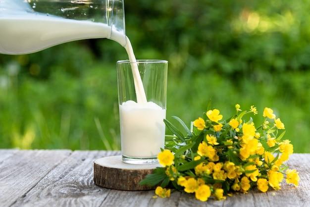 Il latte naturale fresco viene versato in un bicchiere.