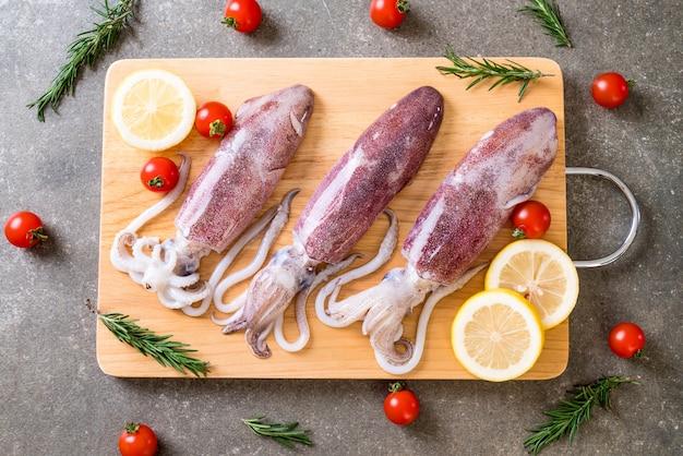 Polpo fresco o calamari crudi su tavola di legno
