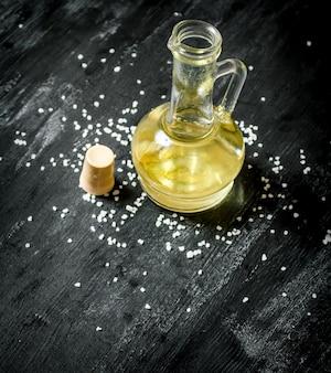 Olio d'oliva fresco in un barattolo di vetro. su sfondo nero rustico.