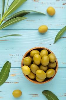 Olive fresche in una ciotola con foglie su sfondo blu con spazio di copia. foto verticale