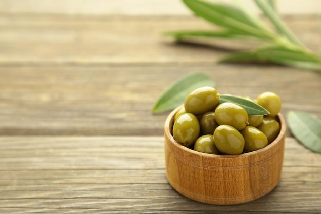 Olive fresche in ciotola con foglie su sfondo grigio. vista dall'alto