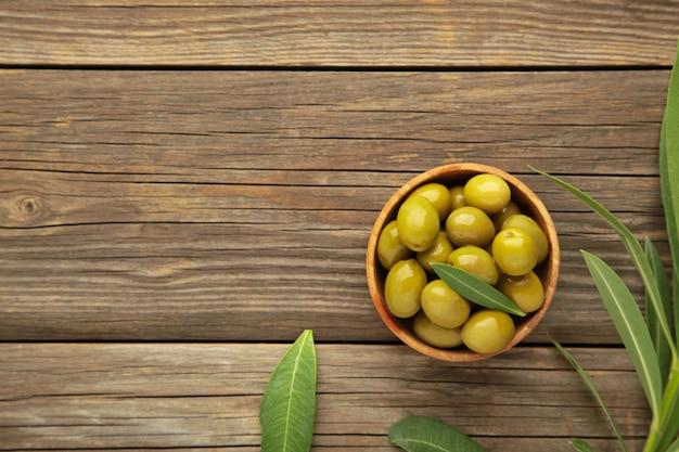 Olive fresche in una ciotola con foglie su sfondo grigio con spazio di copia.