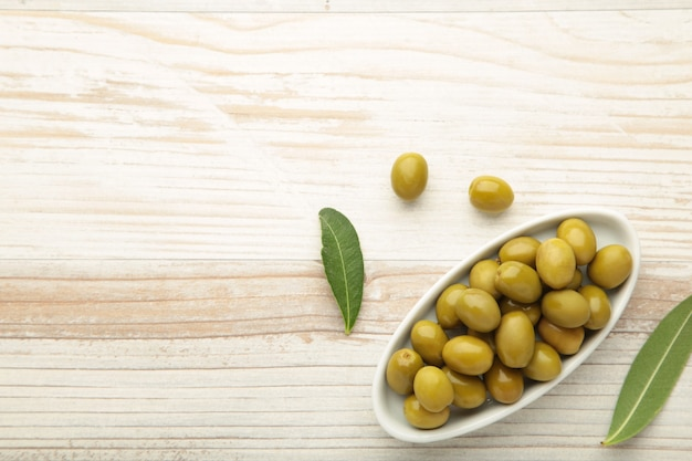 Olive fresche in una ciotola con foglie su sfondo bianco con spazio di copia.