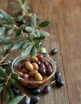 Le olive fresche e la tavola di legno del ramo d'ulivo n si chiudono su con lo spazio della copia