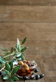 Olive fresche e ramo d'ulivo su legno