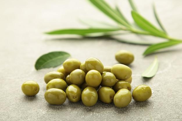 Olive fresche con foglie su sfondo grigio. vista dall'alto