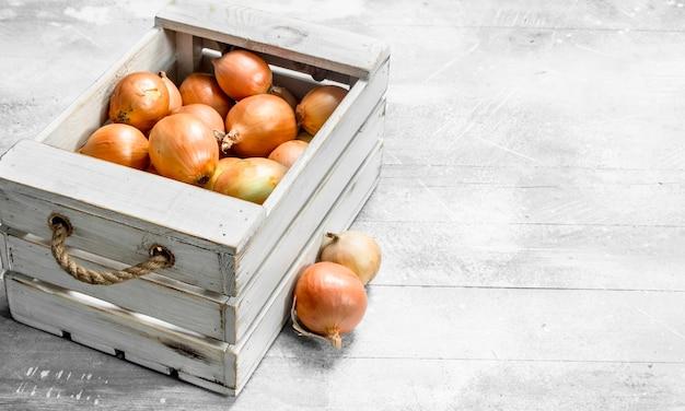 Cipolle fresche nella scatola. su fondo rustico