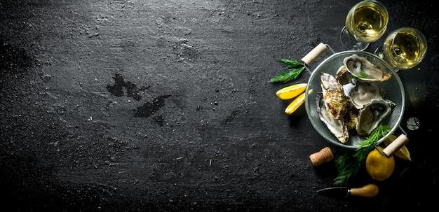 Ostriche fresche aperte in uno scolapasta con vino bianco in bicchieri, aneto e fette di limone sulla tavola di legno nero