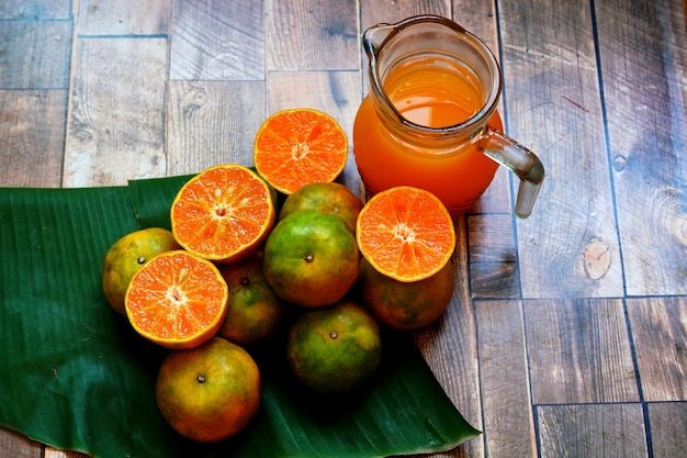 Frutta d'arancia fresca e succo d'arancia su un tavolo di legno