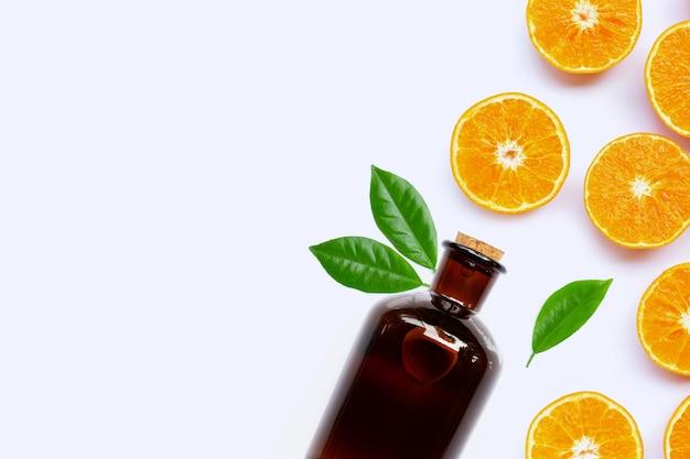 Frutta arancione fresca con bottiglia di olio essenziale sulla superficie bianca.