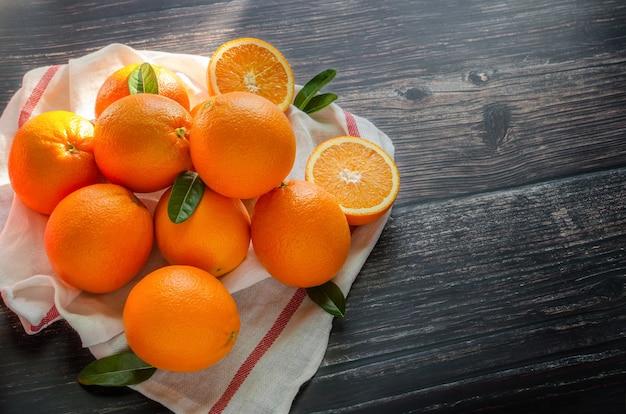Frutti arancioni freschi con foglie sulla tovaglia su tavola di legno e luce solare mattutina.