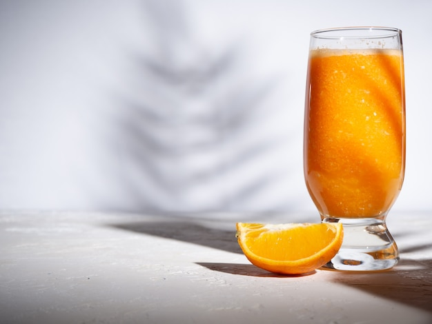 Arancia fresca in una tazza di vetro su uno sfondo bianco con ombre da piante tropicali. copyspace.