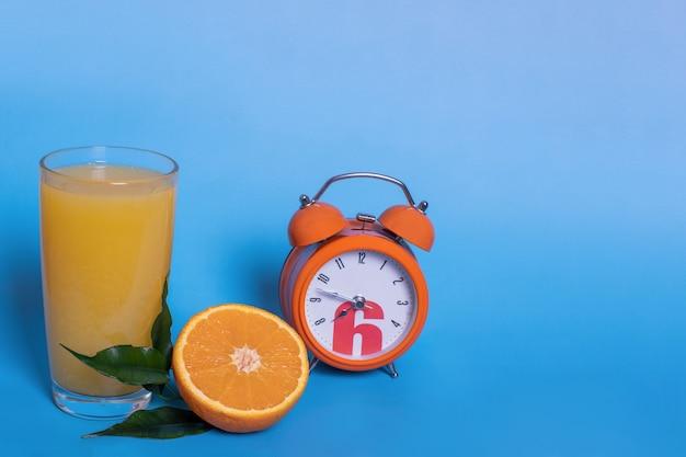 Succo d'arancia fresco in un bicchiere, frutta tagliata a metà e affettata con foglie verdi, sveglia arancione isolata su sfondo blu, copia spazio. è ora di bere un succo