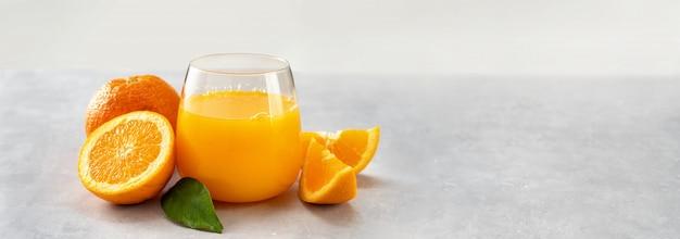 Bicchiere di succo d'arancia fresco e arance