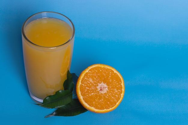 Succo d'arancia fresco in un bicchiere con frutta tagliata a metà e affettata da foglie verdi isolate su sfondo blu, vista dall'alto, copia spazio.