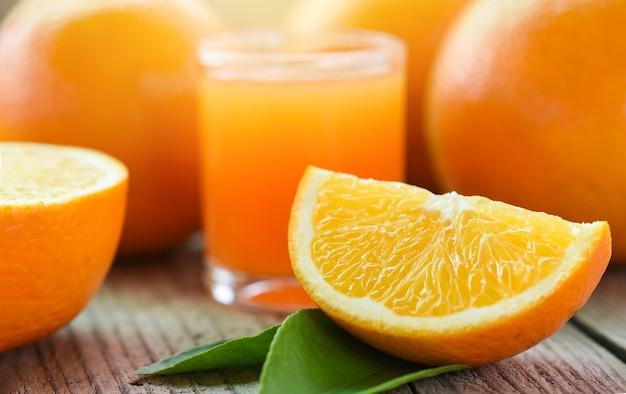 Succo d'arancia fresco nel bicchiere con frutta arancione su frutta sana in legno e fetta d'arancia