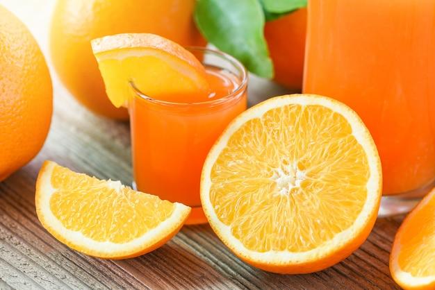 Succo d'arancia fresco nel bicchiere con frutta arancione sulla fetta d'arancia in legno frutti sani