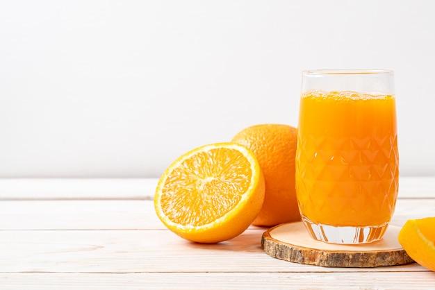Bicchiere di succo d'arancia fresco con arance