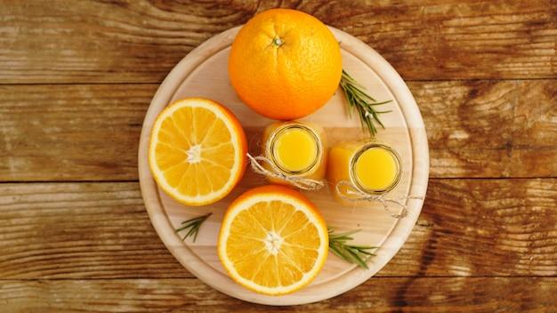 Succo d'arancia fresco sulla tavola di legno su una tavola di legno