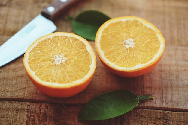 Fetta d'arancia fresca e foglie frutti sani, frutti arancioni con coltello da cucina foglia su legno